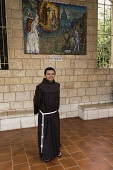 Israel, Galilee, Nazareth, A young Franciscan monk in the plaza in front of the or Basilica of the Annunciationl. Behind him is a mosaic donated by the Vatican.