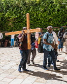 Israel, Jerusalem, Christian pilgrims preparing to walk the Via Dolorosa with a wooden cross begin at the Convent of the Sisters of Zion in the Muslim Quarter of the Old City. The Old City of Jerusale...