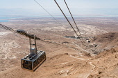Israel, The cable car up to the ruins of the fortress of Masada in the Judean Desert of Israel. Masada National Park is a UNESCO World Heritage Site. The ruins of a former Roman encampment are visible...