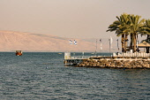 Israel, Tiberius, Sea of Galilee, Boats on the Sea of Galilee and the dock of a shore-side hotel in Tiberius. Across the lake are the Golan Heights, occupied by Israel.