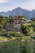 Guatemala, Solola, Lake Atitlan, Spacious villa on the shore with a steep, forested hill behind and lake in foreground.