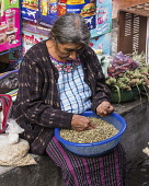 Guatemala, Solola Department, Santiago Atitlan, A Mayan woman wearing traditional dress sorts nuts for sale in the market.