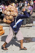 Guatemala, Solola Department, Santiago Atitlan, A young man carries a heavy load of oranges from the market on his back using a tumpline.