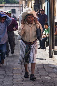 Guatemala, Solola Department, Santiago Atitlan,An older man in traditional dress carries a heavy load  on his back using a tumpline around his forehead.
