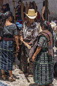 Guatemala, El Quiche Department, Chichicastenango, A  Mayan man in the distinctive outfit from Solola in the Indian market, including a heavy wool rodillera around his waist.  He is buying a new woode...