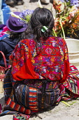 Guatemala, El Quiche Department, Chichicastenango, A woman at the Sunday market  wears the traditional colorful woven huipil or blouse from that town.