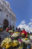 Vendors sell flowers on the steps of the Church of Santo Tomas in Chichicastenango, Guatemala.  The church was built about 1545 on the steps of a Mayan pyramid.