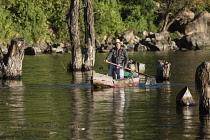 Guatemala, Solola Department, San Pedro la Laguna, A Tzutujil Mayan man in the traditional dress of San Pedro la Laguna paddles his cayuco or fishing canoe on Lake Atitilan.