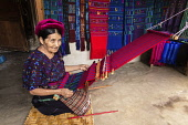Guatemala, Solola Department, Santa Catarina Palopo, An older Cakchiquel Mayan woman weaves fabric on a backstrap loom while kneeling on the floor of her home.