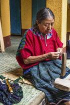 Guatemala, Solola Department, Santa Cruz la Laguna, An older Mayan woman in traditional dress winds thread in preparation for weaving on a back loom.
