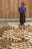 Guatemala, Solola, San Antonio Palopo, A Cakchiquel Mayan woman at her pottery workshop in the traditional dress including the elaborate cinta or hair wrap, woven blue huipil blouse, faja or belt, and...