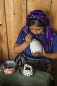 Guatemala, Solola, San Antonio Palopo, A young Mayan woman, wearing typical traditional dress, paints designs on pottery in a workshop.