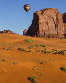 USA, Arizona, Monument Valley, A hot air balloon flying over the red sand dunes at Sand Springs  during Balloon Festival in the  Navajo Tribal Park.