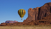 USA, Arizona, Monument Valley, A hot air balloon flying by Spearhead Mesa during Balloon Festival in the Navajo Tribal Park.