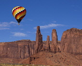 USA, Arizona, Monument Valley, A hot air balloon flying by the Three Sisters during Balloon Festival in the Navajo Tribal Park.