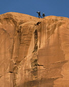 USA, Utah, Moab, A base jumper leaps off the 400 foot vertical face of the Tombstone in Kane Springs Canyon.