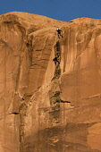 USA, Utah, Moab, A base jumper leaps off the 400 foot vertical face of the Tombstone in Kane Springs Canyon. Note his shadow on the cliff.