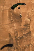 USA, Utah, Moab, A base jumper descends in his parachute off the 400 foot vertical face of the Tombstone in Kane Springs Canyon. Note his shadow on the cliff.