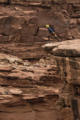 USA, Utah, Moab, A base Jumper jumps off the clifftop 950 feet above the floor of Mineral Canyon.