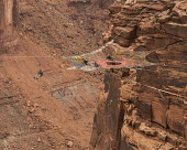 USA, Utah, Moab, Base jumpers prepare to jump from the Mothership Spacenet suspended from the cliffs 950 vertical feet above the valley floor at Mineral canyon.  Another jumper rides the zipline from...