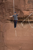 USA, Utah, Moab, A young man slacklining or highlining hundreds of feet above Mineral Canyon during a highline gathering.