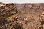 USA, Utah, Moab, A group of slackliners play on the Space Net hundreds of feet above Mineral Canyon during a highline gathering. Behind are several long slacklines over the canyon.