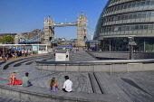 England, London, Tower Bridge with people enjoying Summer sunshine at the Scoop. which is a sunken entertainment amphitheatre next to City Hall.