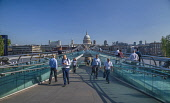 England, London, City workers crossing the Millennium Bridge with the dome of St Paul's Cathedral in the background.
