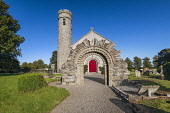 Republic of Ireland, County Kildare, Castledermot, Romanesque doorway in front of St James Church which is Church of Ireland and a 10th century Round Tower in the background.