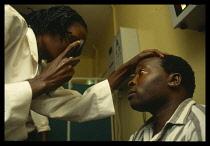 Uganda,Jinja, Eye examination in Jinja Hospital.  Female doctor and male patient.