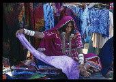 India, Goa, Anjuna, Textile stall at the flea market  female stall holder wearing a pink sari and silver jewellery unrolling a piece of violet coloured cloth.