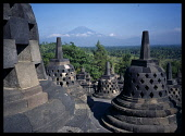 Indonesia, Java, Central, Borobudur Temple ruins.  Buddhist monument constructed in the early 9th century latticed stupas on the upper circular terraces, Mount Merapi in the distance.