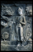Indonesia, Java, Borobudur, Detail of relief carving on wall of multi tiered Buddhist stupa depicting standing Buddha and flowers.