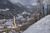 Germany, Bavaria, Berchtesgaden, Stiftskirche and Pfarrkirche St Andreas from the snow covered Brine Line Cliff Walk above the town.