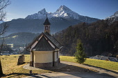 Germany, Bavaria, Berchtesgaden, The Chapel of the Beatitudes above the town on Lockstein Hill, rear view with the snow covered Watzmann Mountain in the distance.