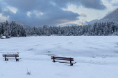 Germany, Bavaria, Berchtesgaden, Berchtesgadener Alps,  Snow covered and frozen Lake Hintersee with seats by the lakeside.