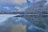 Germany, Bavaria, Berchtesgaden, Berchtesgadener Alps, Partially snow covered and frozen Lake Hintersee with reflection of sky, hillside and clouds in the unfrozen section.