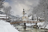 Germany, Bavaria, Ramsau village, famous vista of the Church of  St Sebastian with the footbridge over the Ramsauer Ache river in a snow covered landscape.