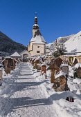 Germany, Bavaria, Ramsau village,  The Church of  St Sebastian with its graveyard in a snow covered landscape.
