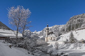 Germany, Bavaria, Ramsau village, famous vista of the Church of  St Sebastian with the Ramsauer Ache river in a snow covered landscape.