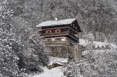 Germany, Bavaria, Ramsau village, Typical Alpine house in a snow covered landscape above the village.