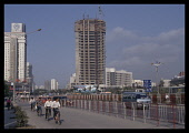 China, Guangdong, Shenzen, Cyclists and cars on road in front of skyscraper under construction.