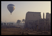 Egypt, Luxor, Tourist hot air balloon over ruined temple in early evening light.