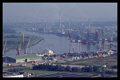 France, Normandy, Seine-Maritime, Rouen, View over docks with cranes and container vessels on the River Seine to the west of Rouen with capacity for ocean-going ships.