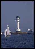 Germany, Baltic, Kiel Canal, Lighthouse near canal entrance and passing yacht.