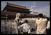 China, Beijing , Tiananmen Square, Chinese tourists having their photograph taken in front of lion statue.
