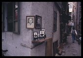 China, Guangdong, Guangzhou, Backstreet with shrine to ancestors on the corner and pedestrians walking past.