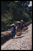 China, Guangxi, Three women on the road to market carrying baskets on poles over their shoulders.