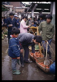 China, Hunan, Huaihua, Man and young boy buying carrots in a street market on a rainy day.