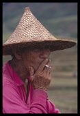 China, Hainan Island, People, Farmer in conical hat smoking a cigarette, head and shoulders three-quarter profile portrait.